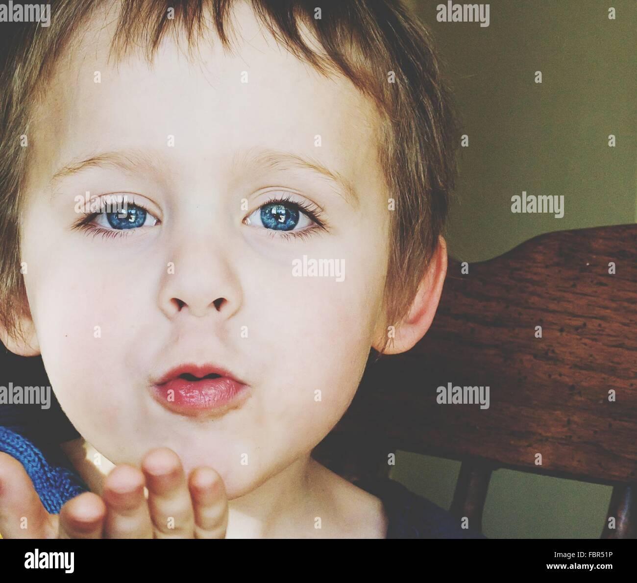 Porträt von niedlichen Blue Eyed Boy weht einen Kuss Stockbild