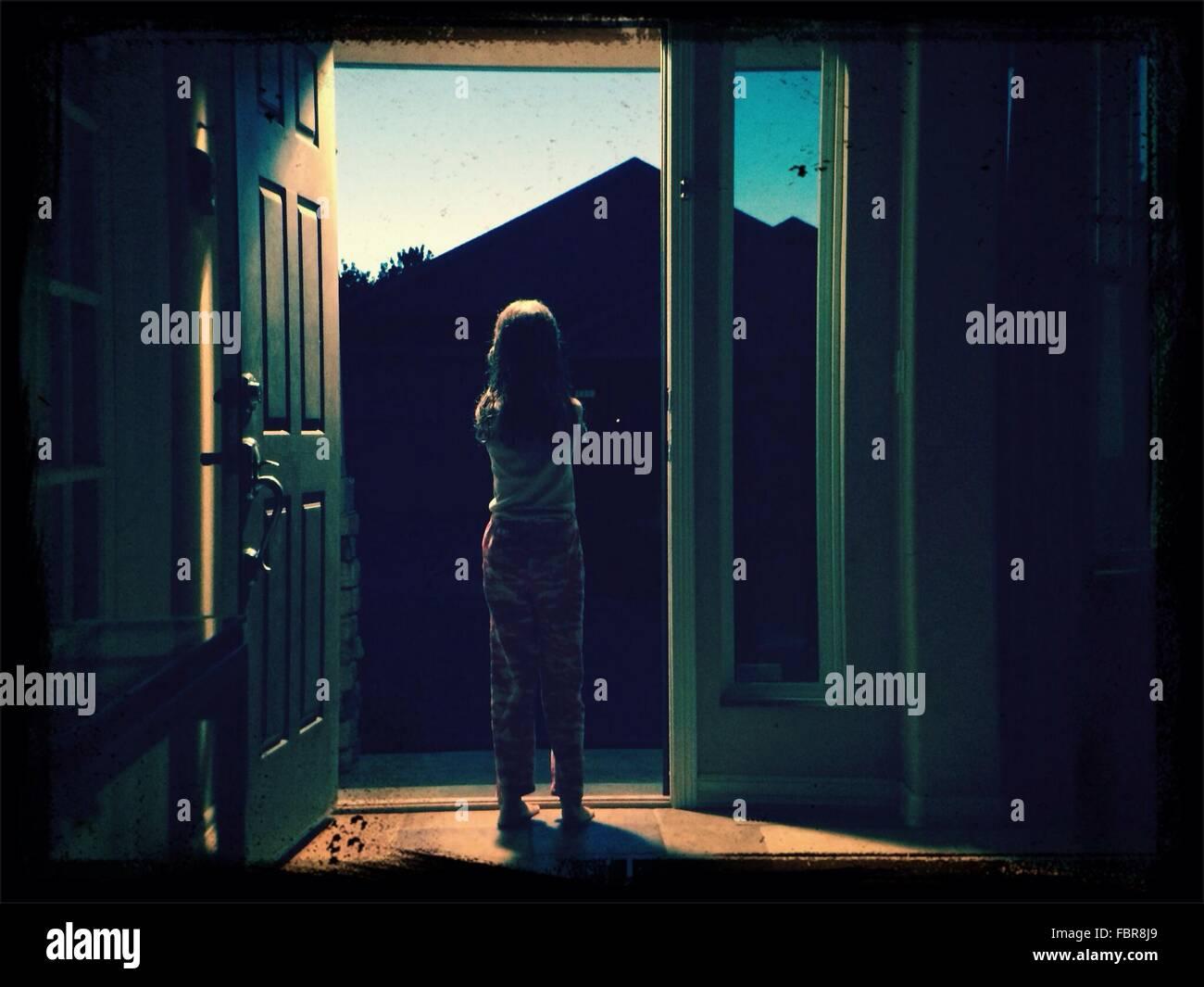 Voller Länge Rückansicht des Mädchen steht am Eingang zu Hause Stockbild