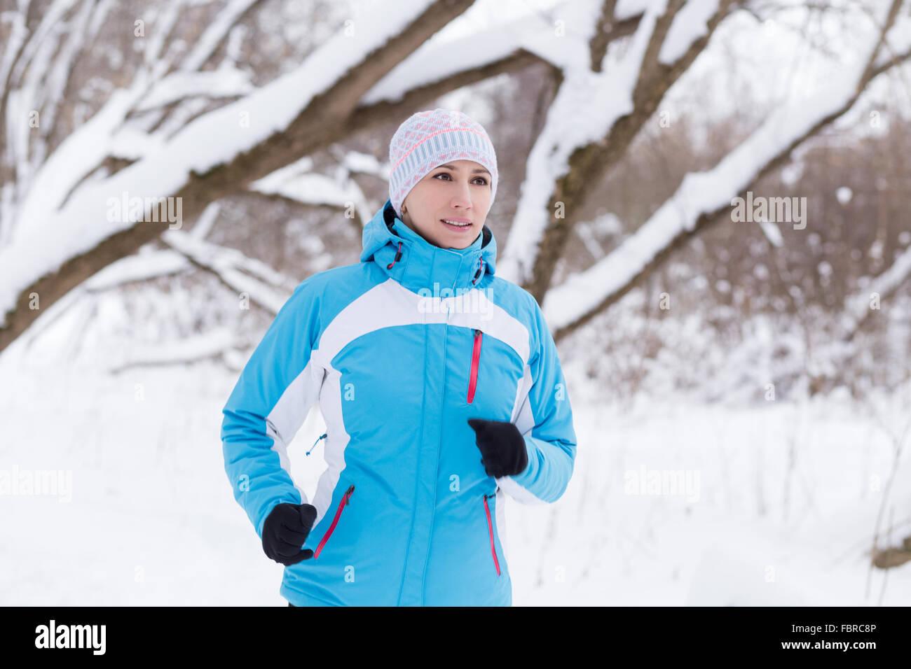 Junge schlanke Frau im Winter Park Joggen. Kaukasische Mädchen in Sportbekleidung ausgeführt Stockbild