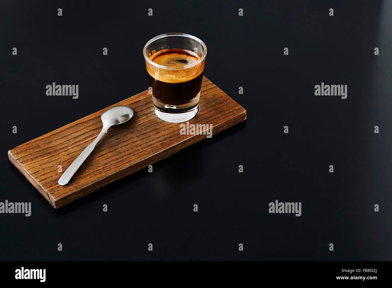 Nahaufnahme von einem Schuss Espresso auf Holzplatte Stockbild