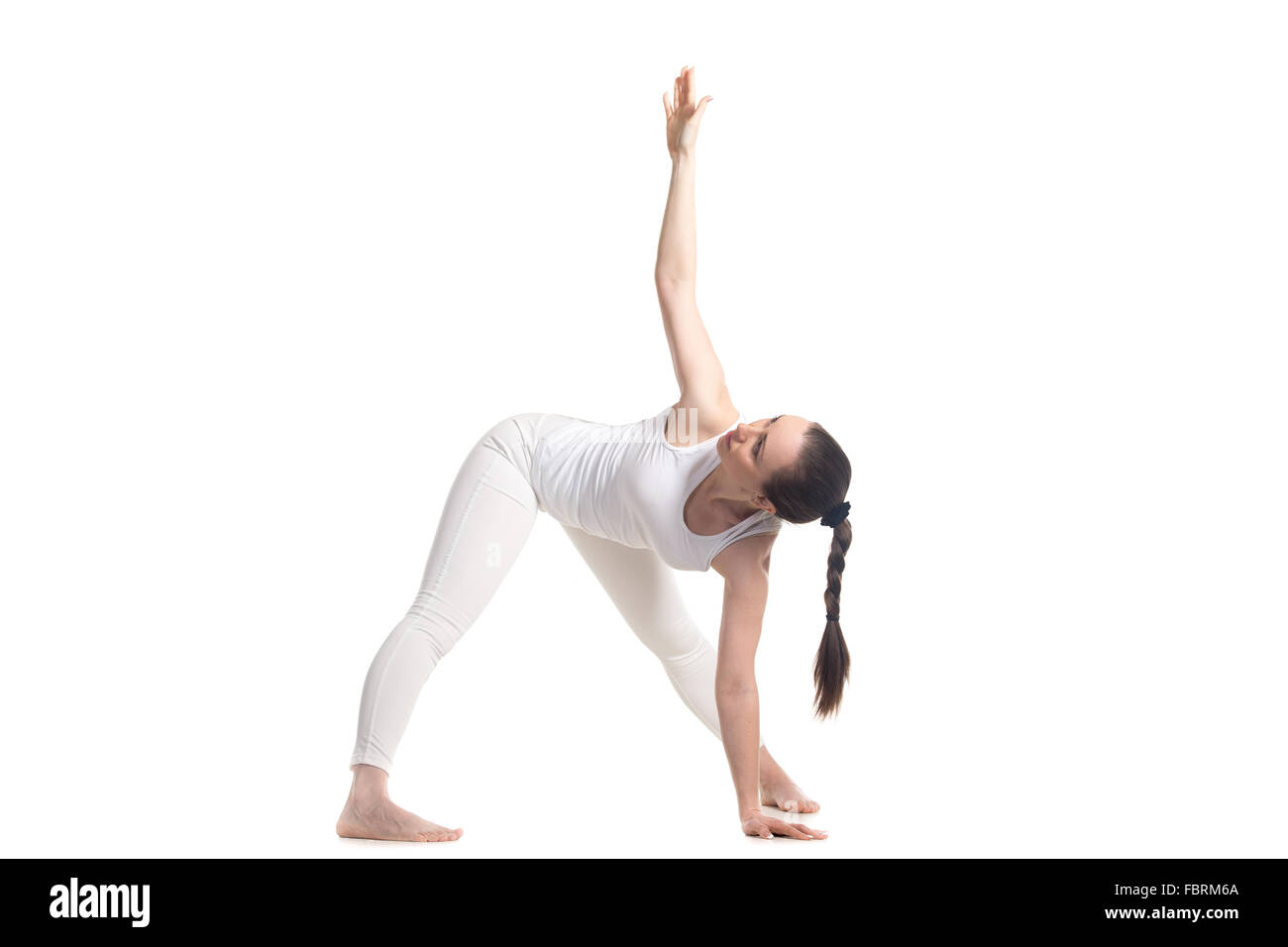 Sportlich schöne junge Frau im weißen Sportbekleidung stehen in Variante des Dreieck-Yoga pose, Studio Stockbild