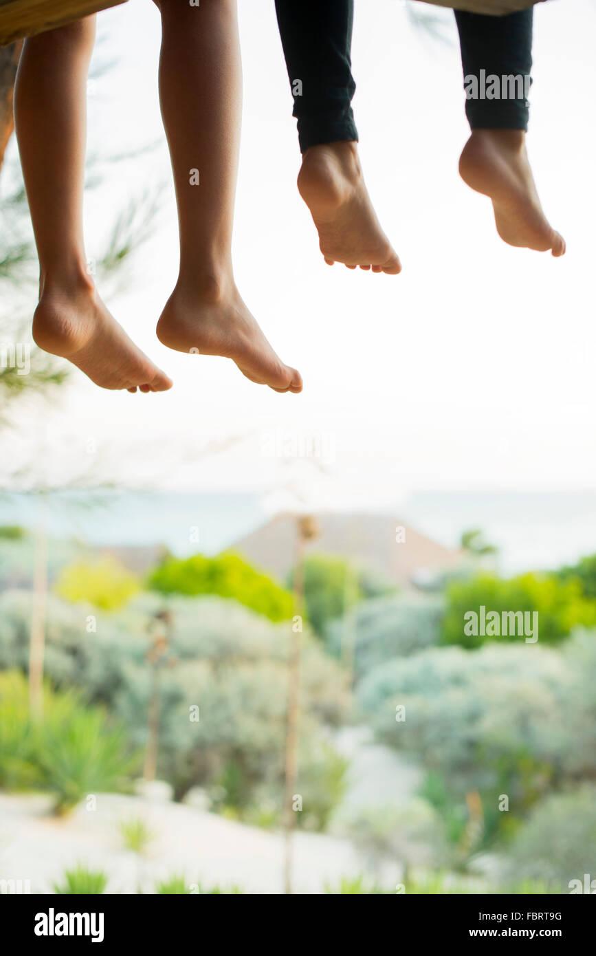 Kinder sitzen Seite an Seite mit nackten Füße baumelten Stockbild