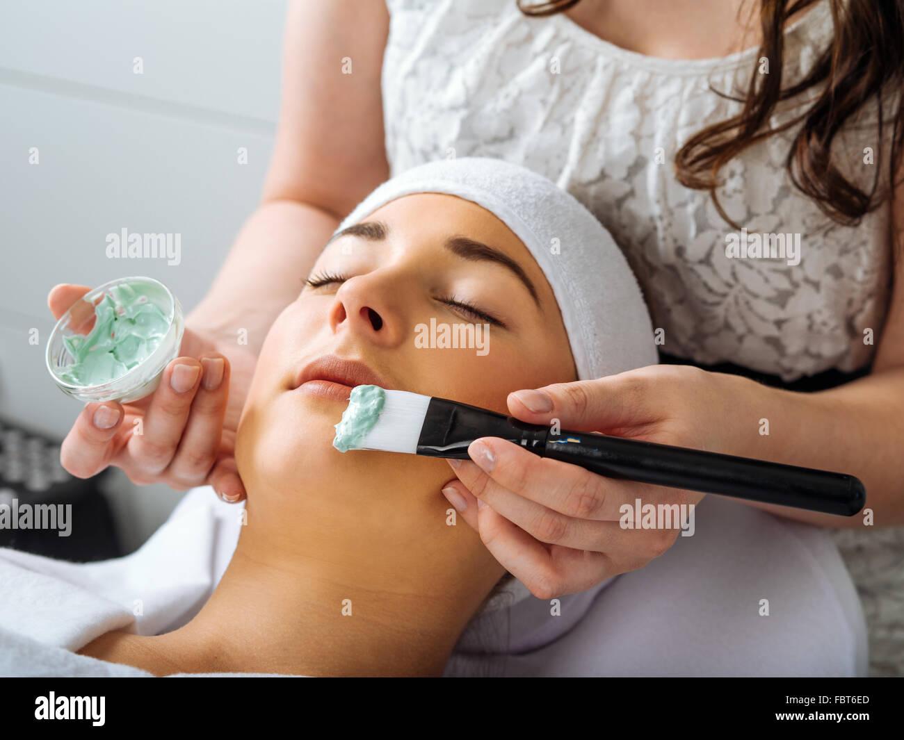 Foto von einem jungen schönen Mädchen erhalten eine grüne Gesichtsmaske in Spa-Beauty-Salon. Stockbild