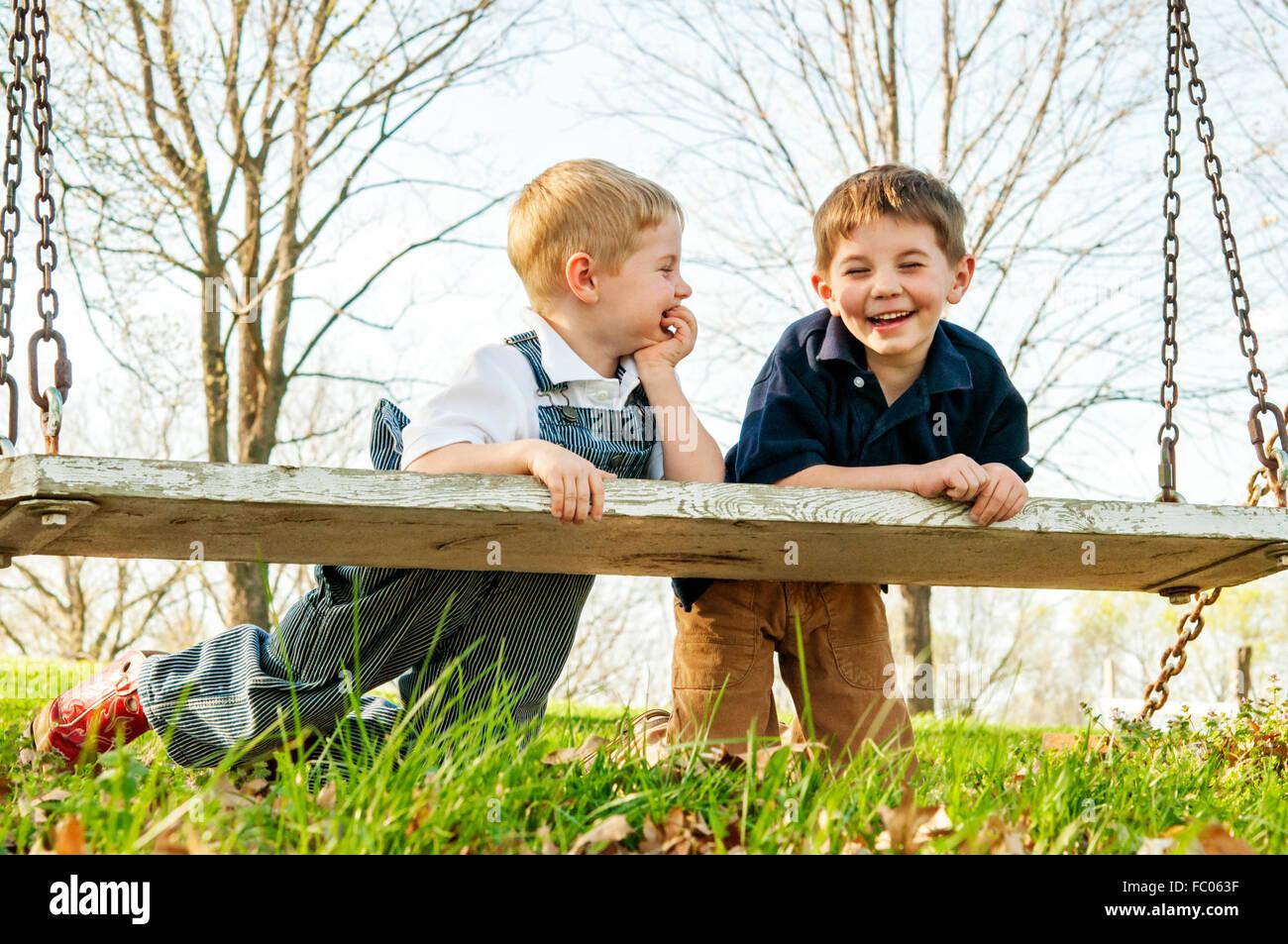 Zwei jungen stützte sich auf schwingen gemeinsam lachen Stockbild