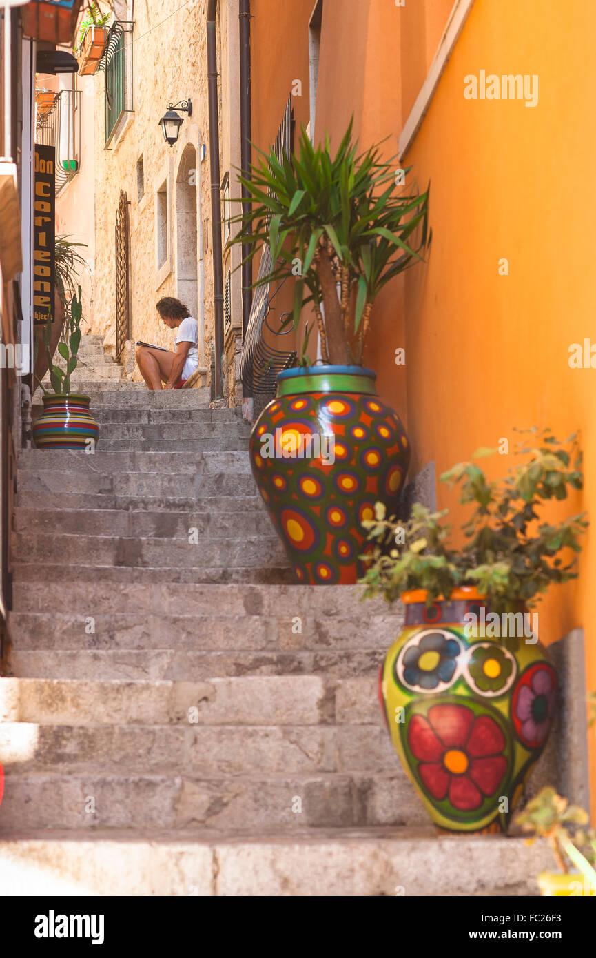 Taormina Sizilien, liest ein Mann allein in einer engen Straße in der Altstadt von Taormina, Sizilien. Stockbild