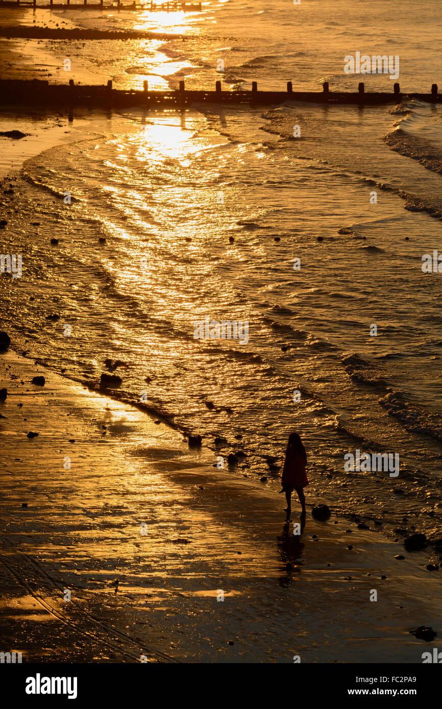 Person zu Fuß am Strand entlang während des Sonnenuntergangs über Cromer Norfolk England Stockbild