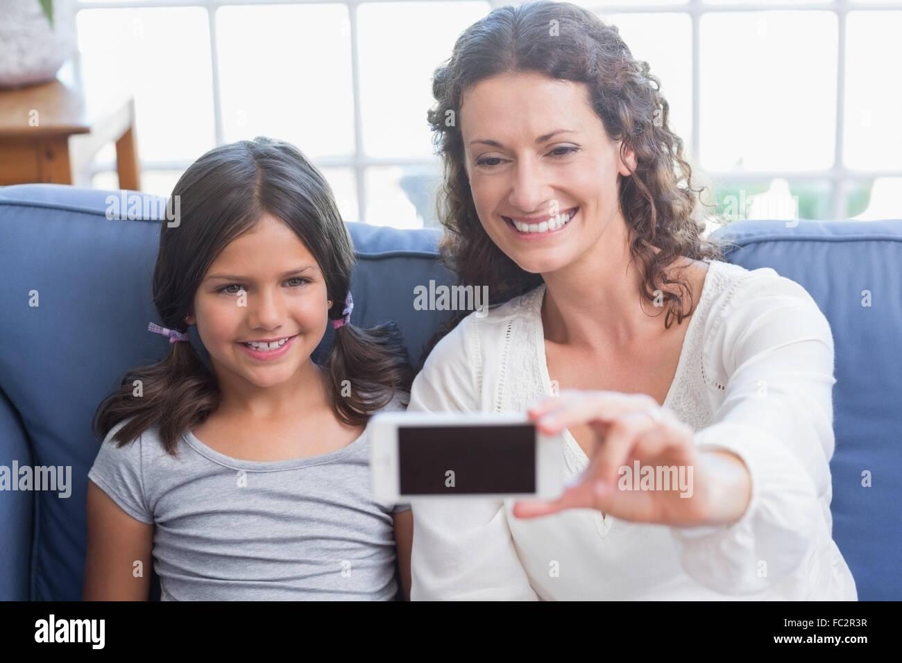 Glückliche Mutter und Tochter sitzen auf der Couch und