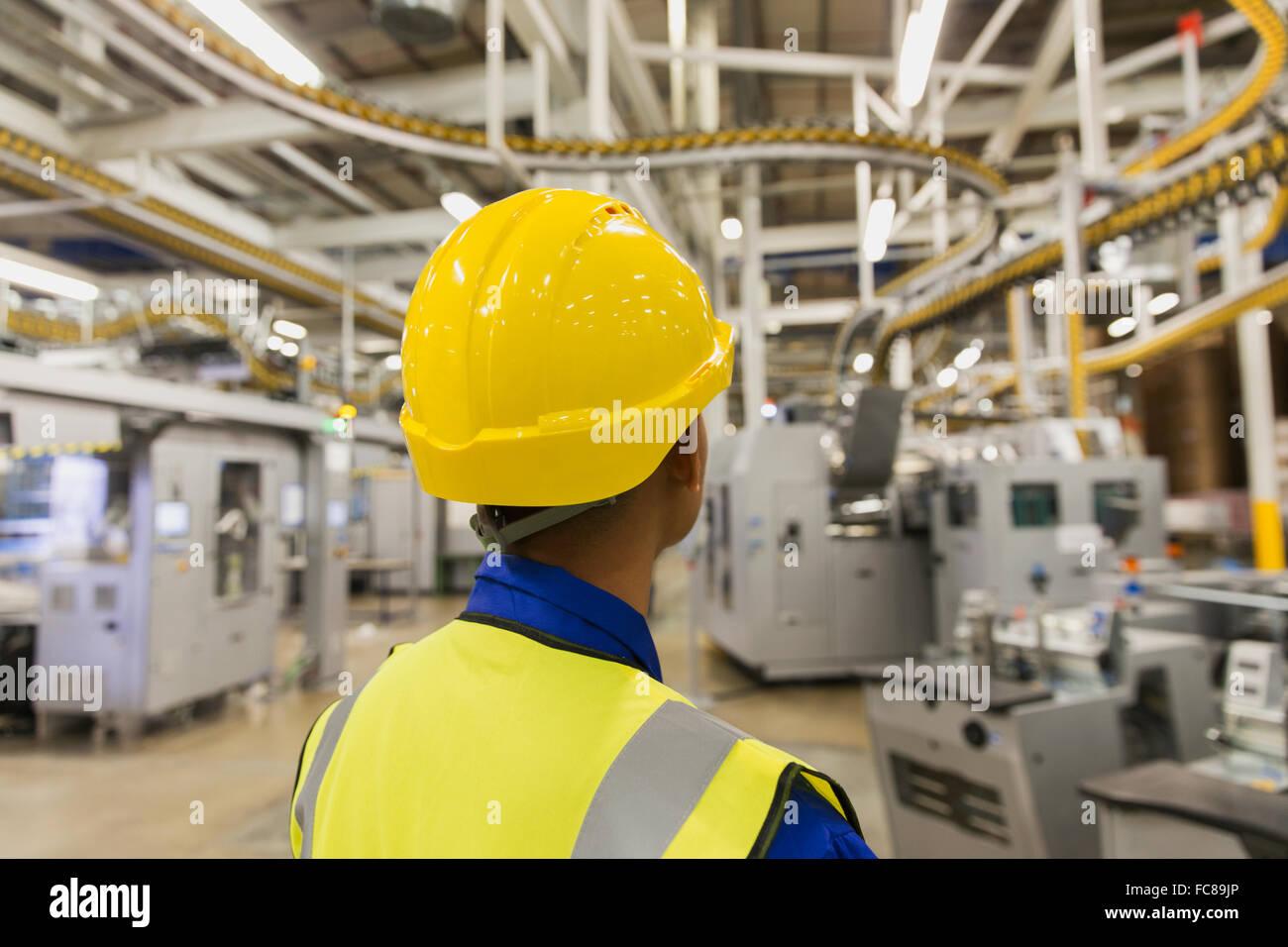 Arbeiter in Akkubohrschrauber beobachten Druckmaschine Förderbänder und Maschinen in Druckerei Stockfoto