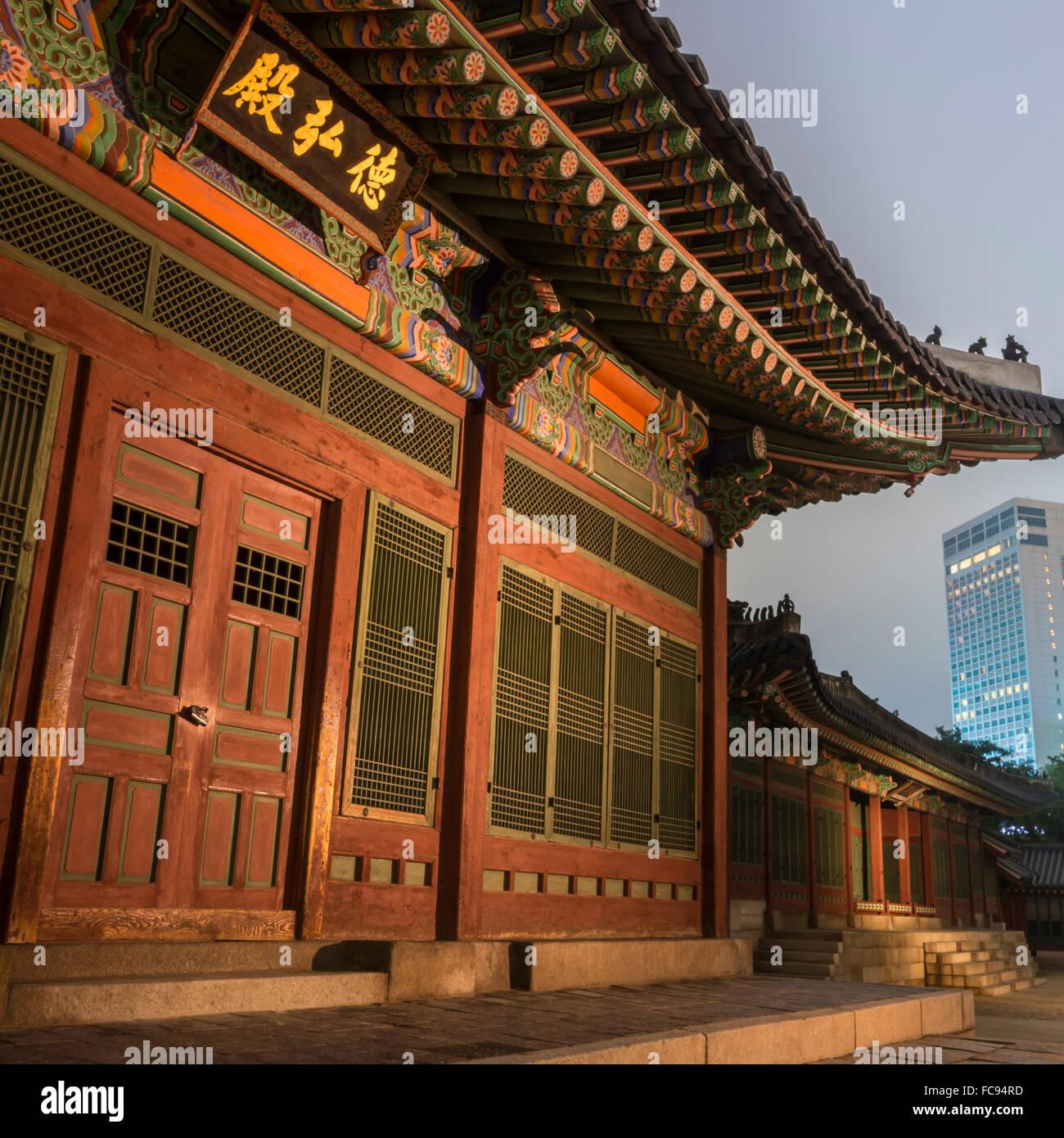 Deoksugung Palast, traditionelle koreanische Gebäude, beleuchtet in der Dämmerung, mit modernen Gebäude Stockbild