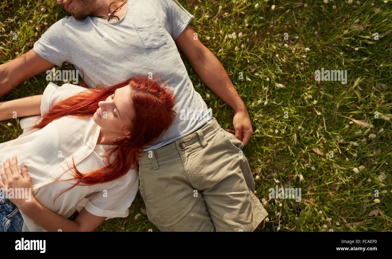 Junge Frau mit ihrem Freund auf dem Rasen liegen. Draufsicht des jungen Paares entspannende auf dem Rasen mit Textfreiraum. Stockbild
