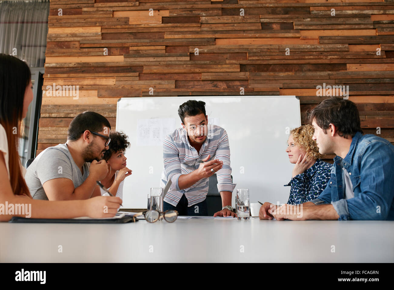 Brainstorming in einem Sitzungssaal Kreativbüro. Junge kreative Menschen am Tisch sitzen und neue Projekte Stockbild