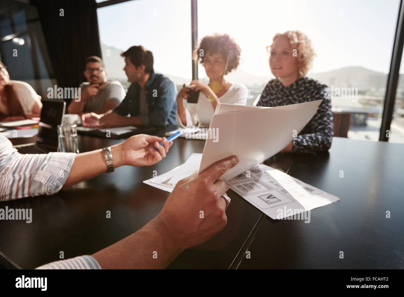 Papiere in Händen des jungen Mannes, Businessplan, seinem Kreativteam zu erklären. Kreativ-Profis treffen Stockbild