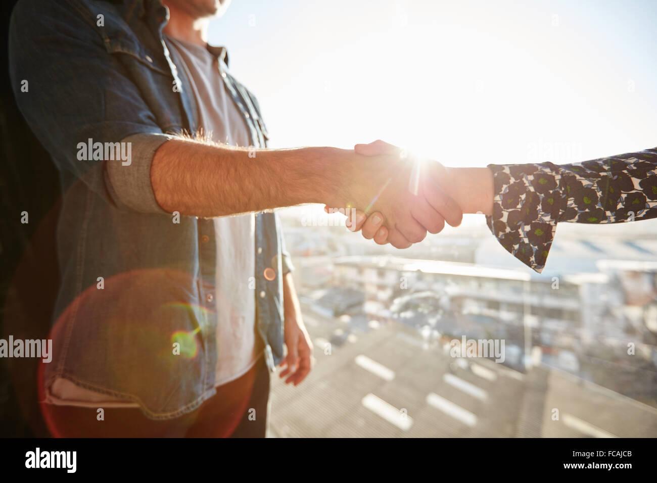 Nahaufnahme von Händeschütteln von Mann und Frau mit Objektiv flare. Handshake an einem sonnigen Tag im Stockbild