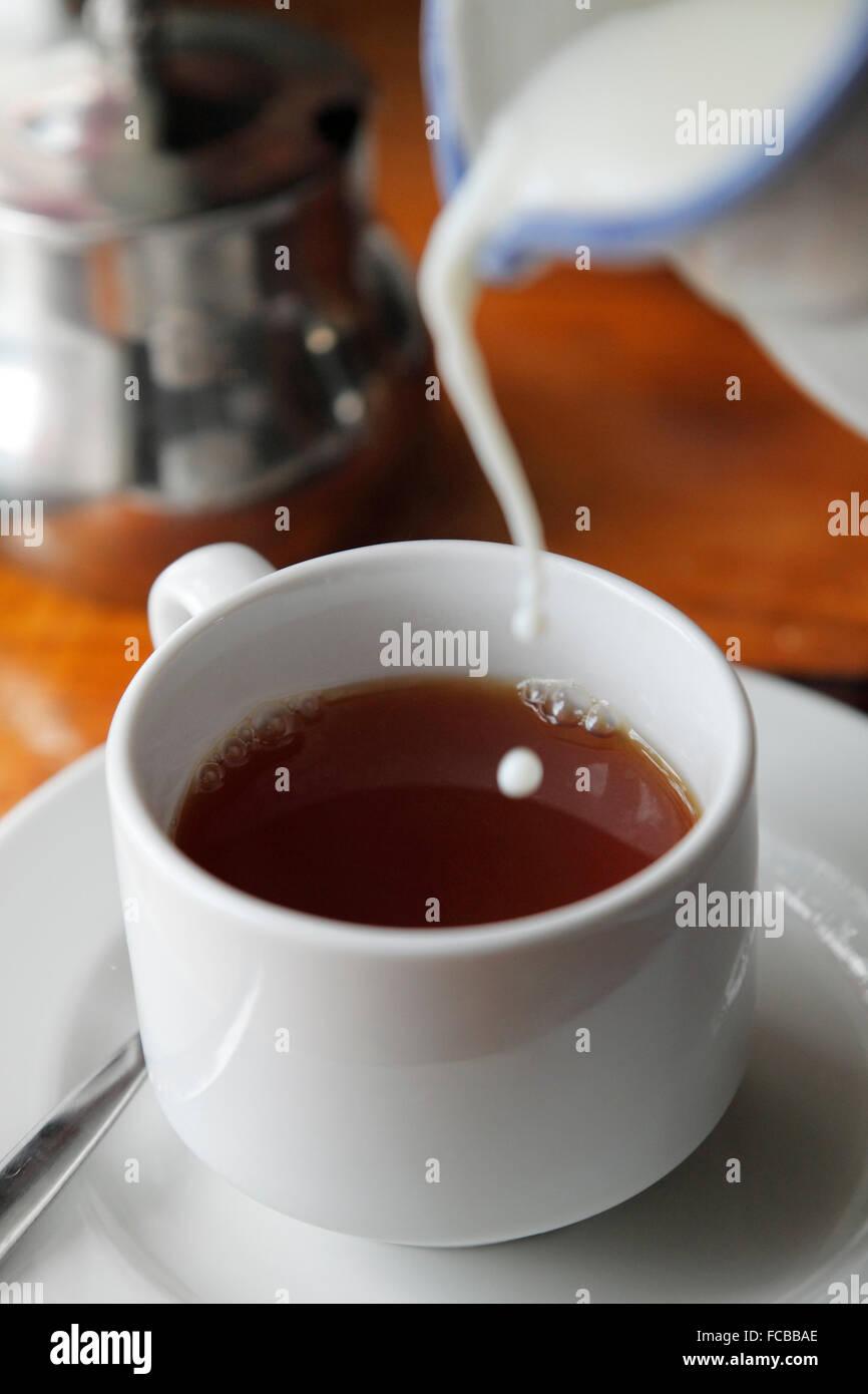 Milch in den Kaffee gießen Stockbild