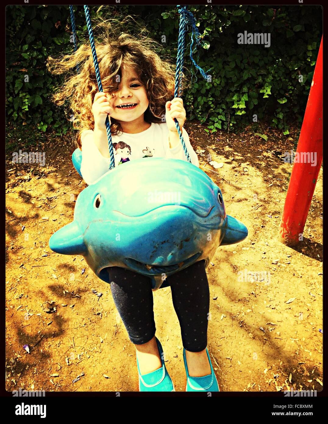 Mädchen genießen Swing Ride auf Spielplatz Stockbild