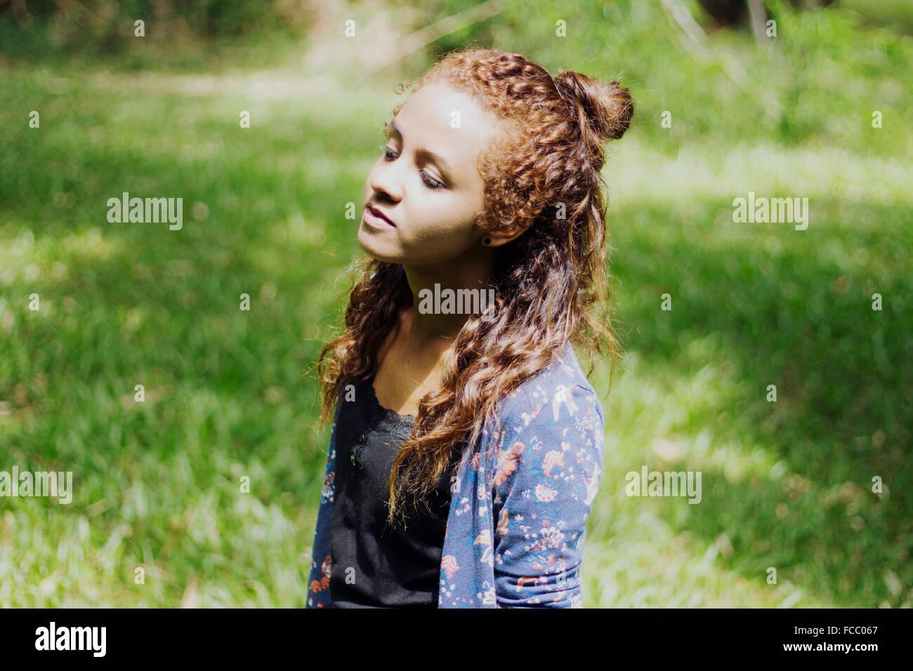 Seitenansicht einer jungen Frau gegen Grasgrün Stockbild