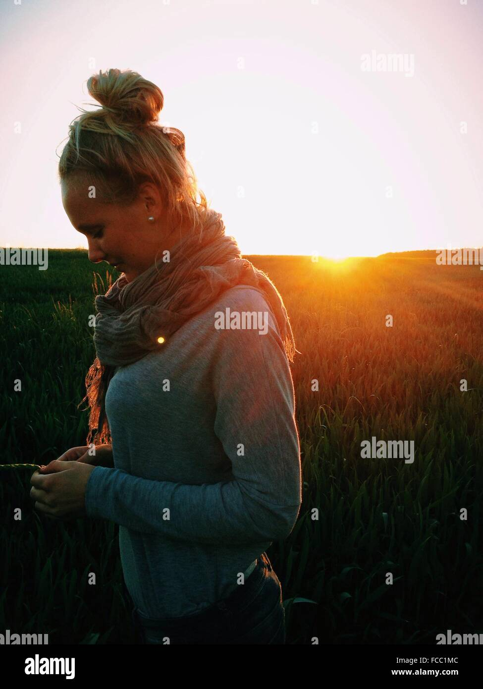 Seitenansicht der jungen Frau auf Feld bei Sonnenuntergang Stockbild