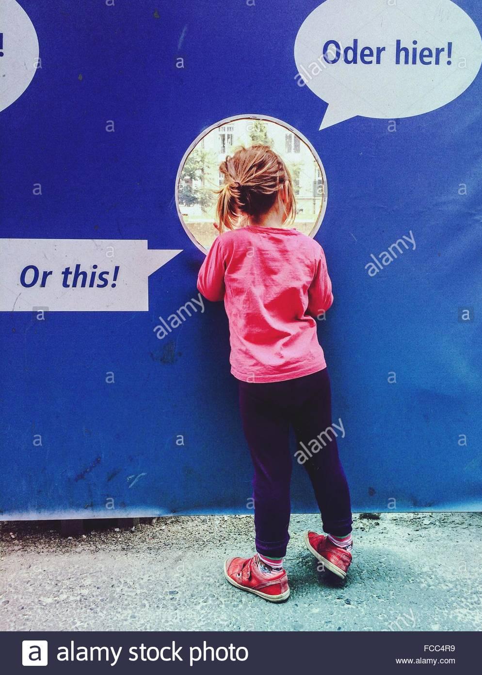 Rückansicht des Mädchens durch kreisförmige Fenster im freien Stockbild