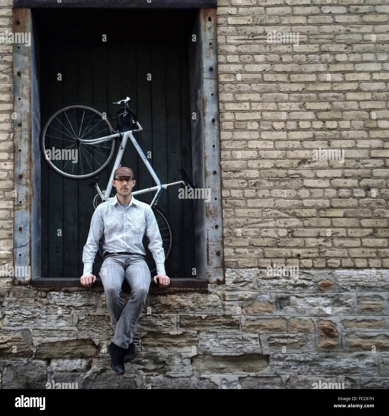 Porträt eines jungen Mannes, der am Eingang sitzt Stockbild