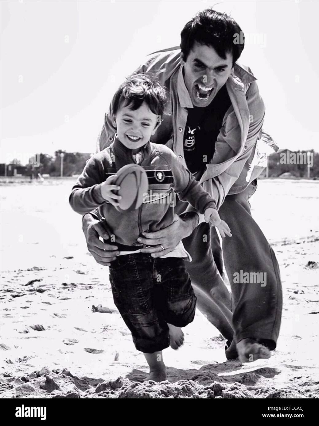Vater, spielen Rugbyspiel mit Sohn am Strand Stockbild