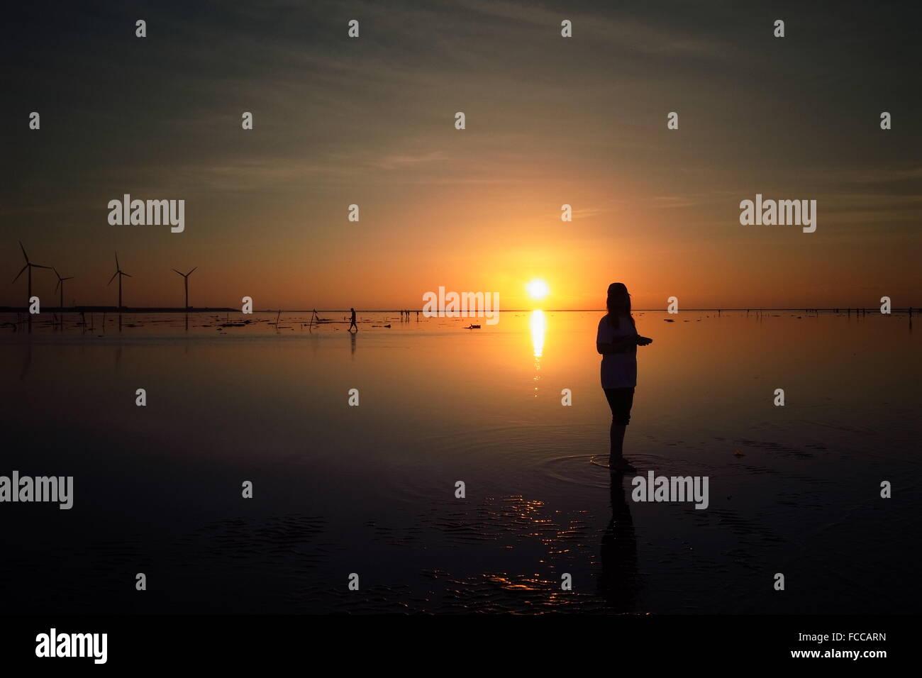 Silhouette Frau stehen am Strand bei Sonnenuntergang Stockbild