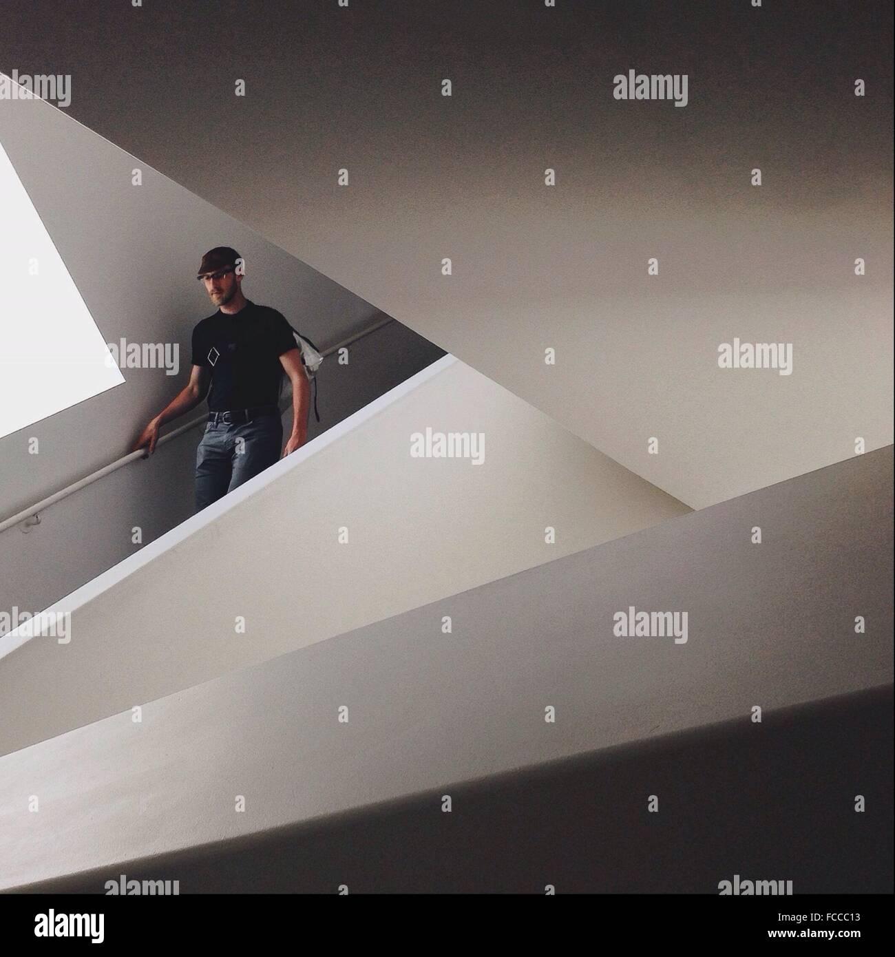 Mann zu Fuß hinunter auf Treppen In modernem Gebäude Stockbild