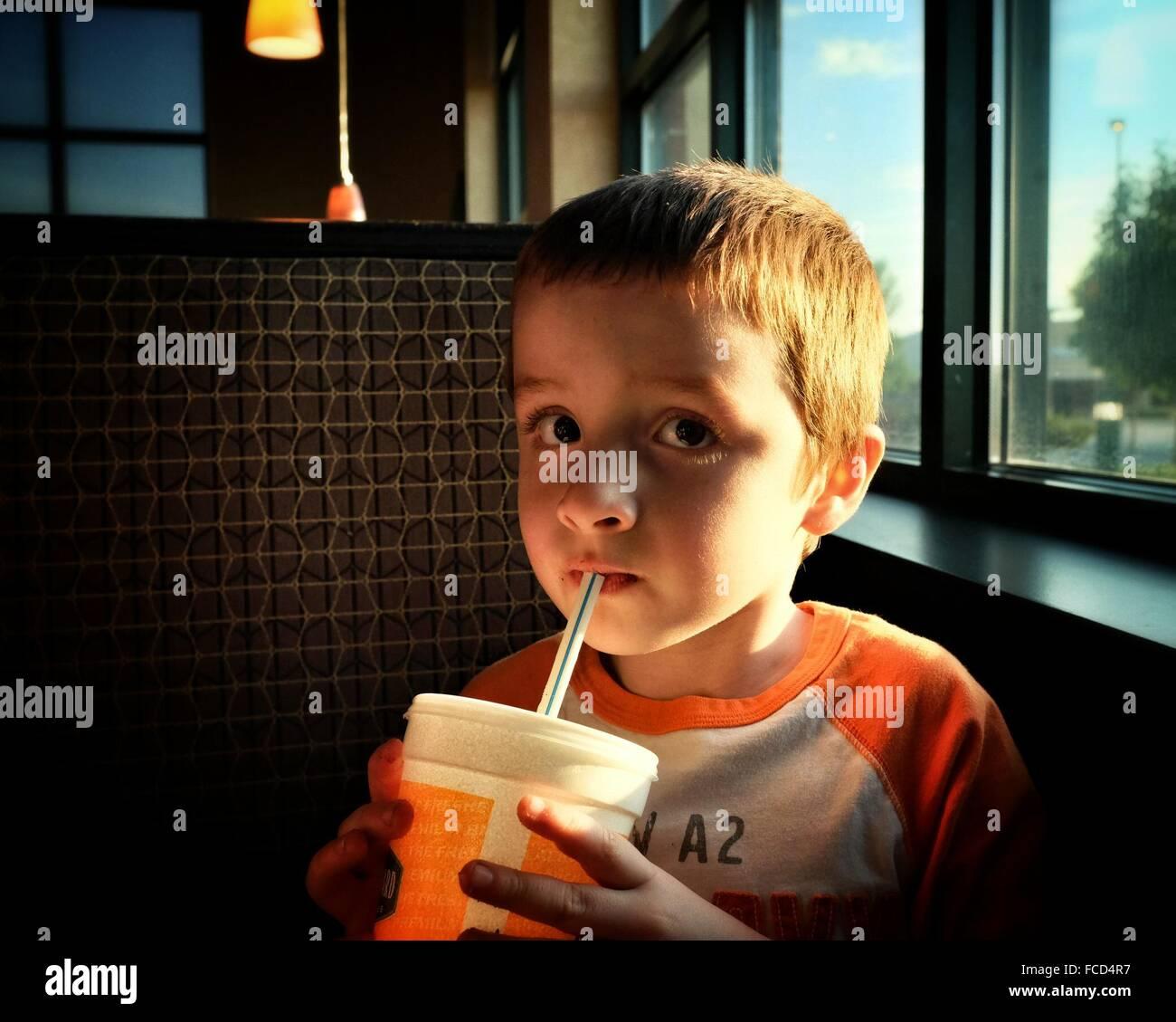 Close-up Portrait von niedlichen jungen trinken beim Sitzen im Restaurant Stockbild