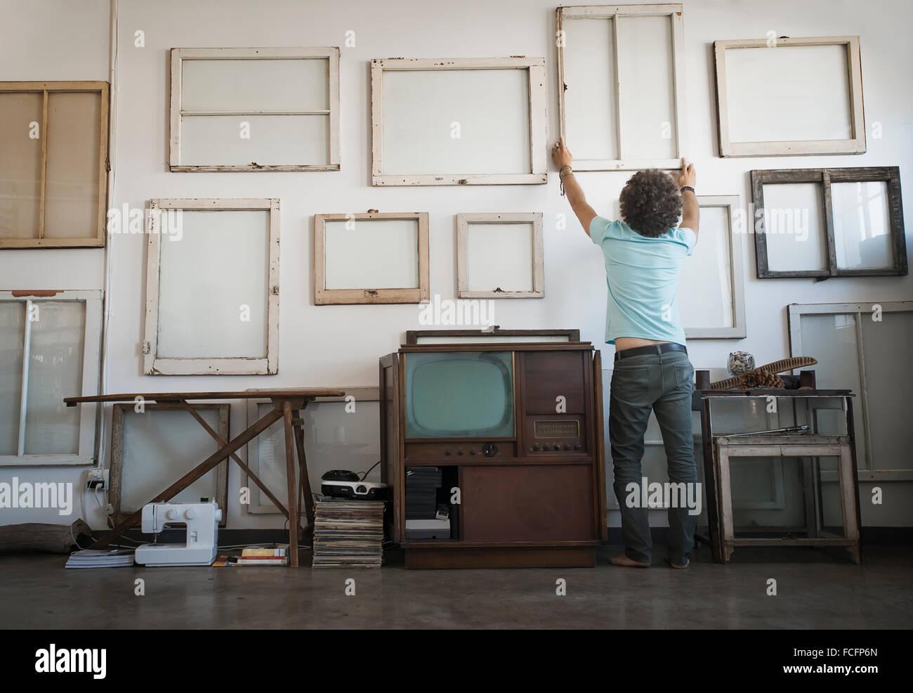 Loft-Dekor. Ein Mann hängen gerahmte Bild Gemälde an der Wand. Stockbild