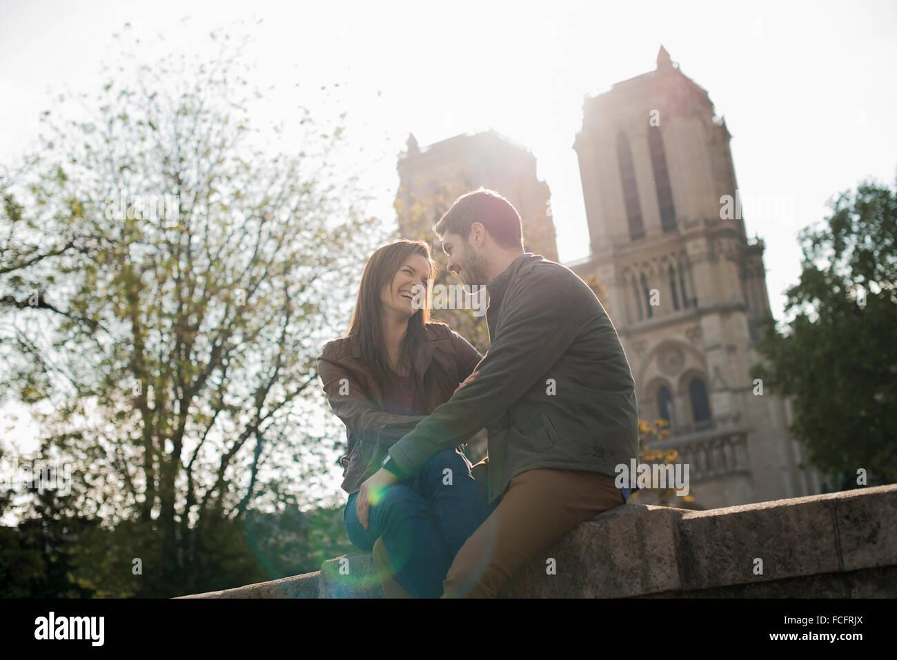 Ein paar in eine romantische Stimmung, Seite an Seite mit Arme umeinander außerhalb der Kathedrale Notre Dame Stockbild