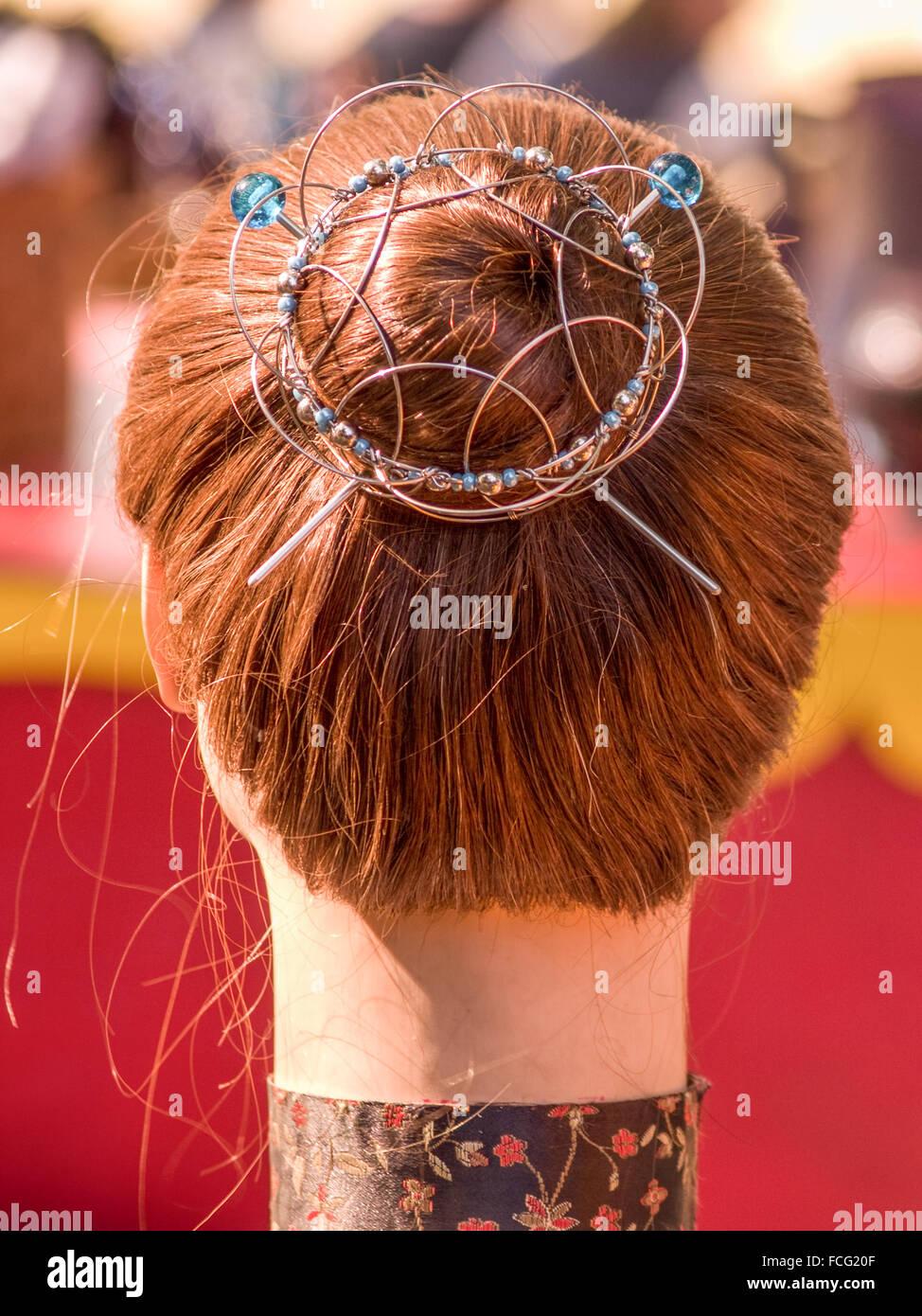 Hals und Kopf der Puppe mit roten Haaren in einem Brötchen Wabbel durch Draht Haarnadeln beim Renaissance Festival Stockfoto