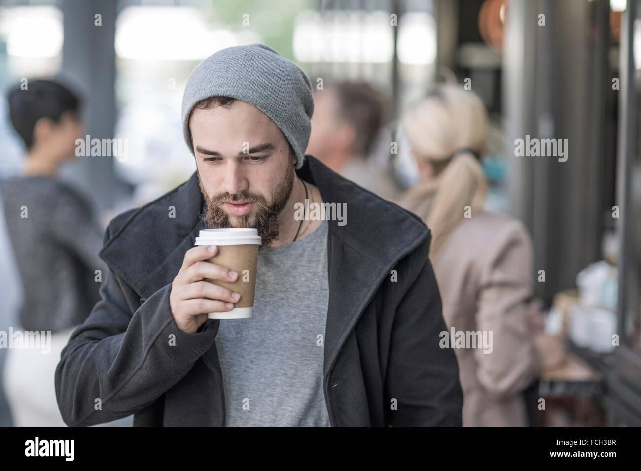 Junger Mann trinken Kaffee zum mitnehmen in der Stadt Stockbild