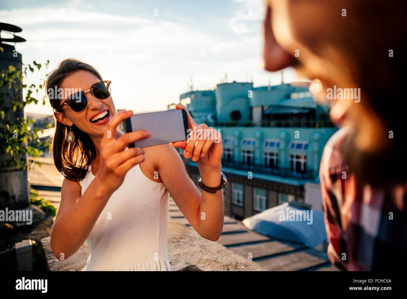Austria Wien-Porträt der lächelnde junge Frau, ein Foto von ihrem Freund auf einer Dachterrasse Stockbild