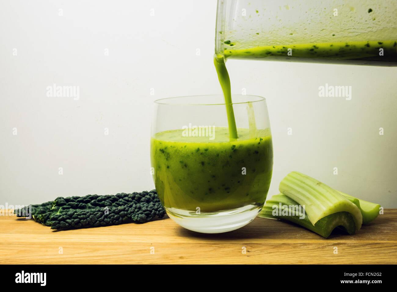 Gießen Sie ein Glas grün Sirtfood Kale smoothie Stockbild