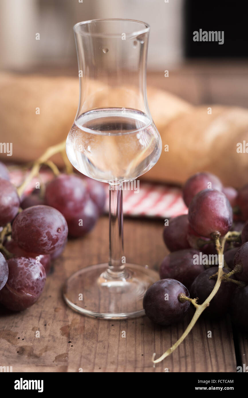 italienischen Grappa mit Trauben und Brot auf Holztisch Stockfoto