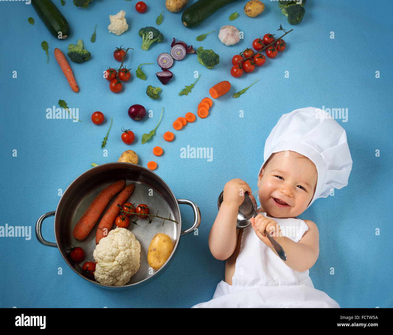 Baby Boy in Koch Hut mit Kochen Pfanne und Gemüse Stockbild