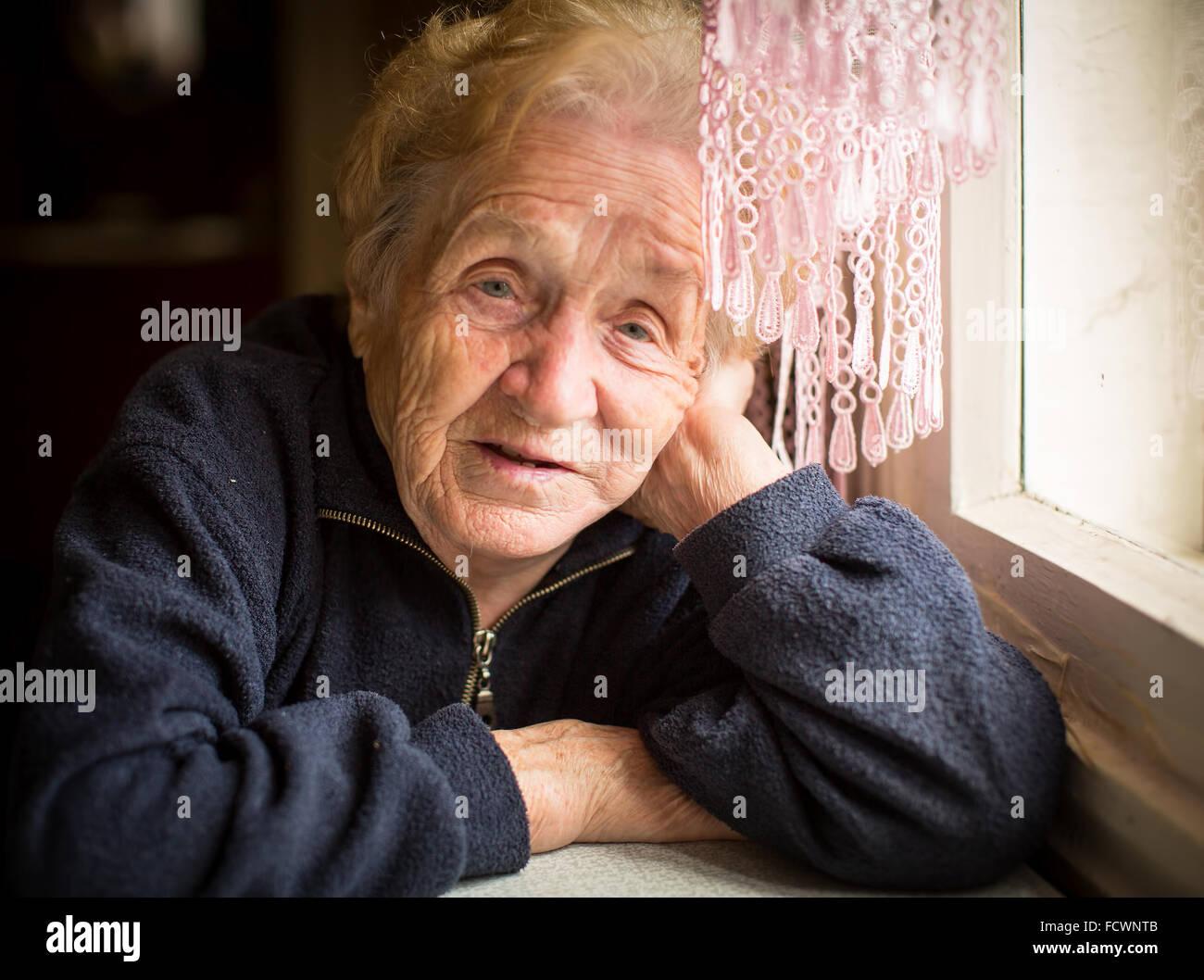 Eine ältere Frau sitzt in der Nähe des Fensters. Stockbild
