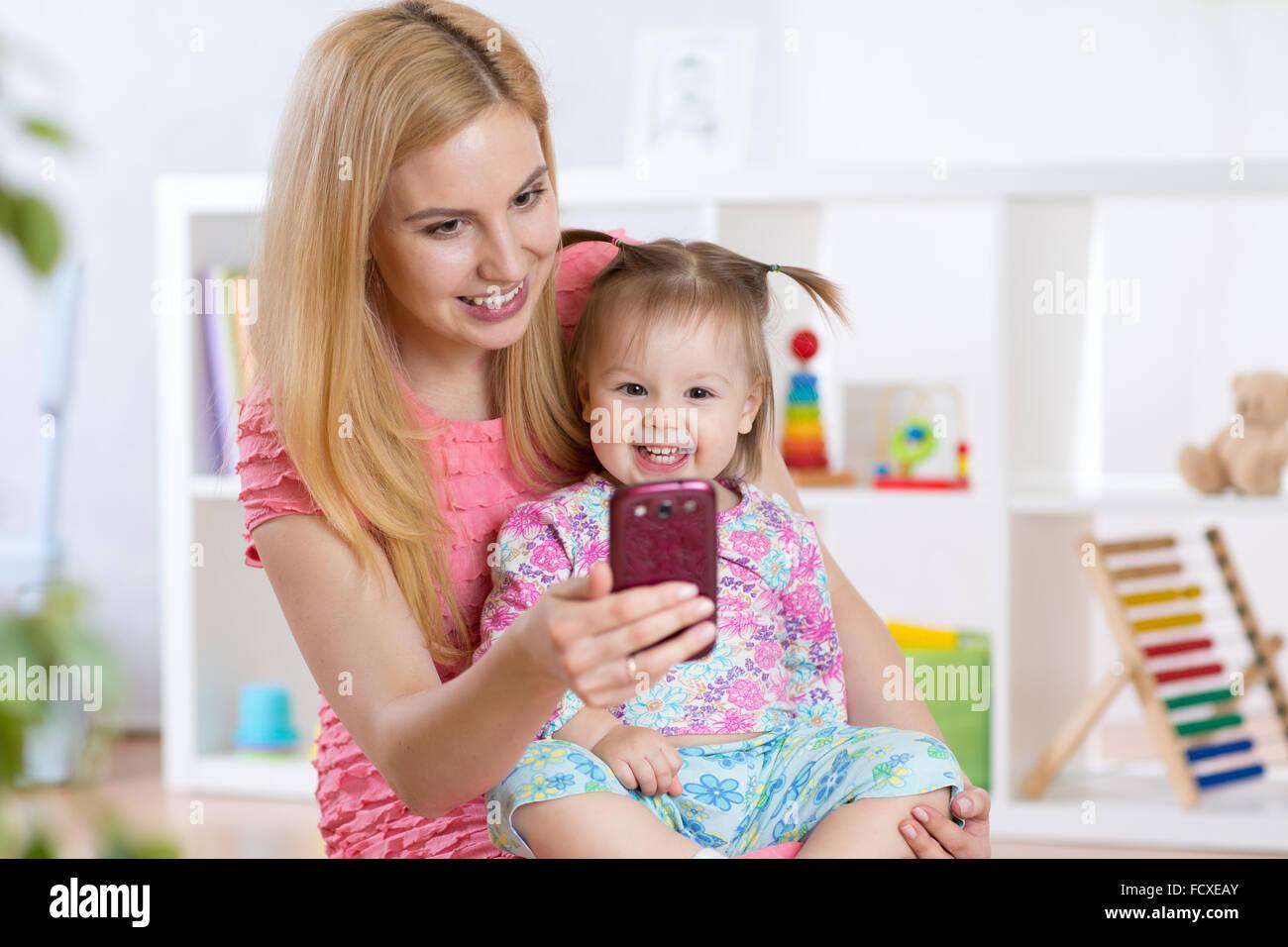 Mutter und ihr kleines Kind Mädchen nehmen Selfie auf einer Decke im Kinderzimmer Stockbild