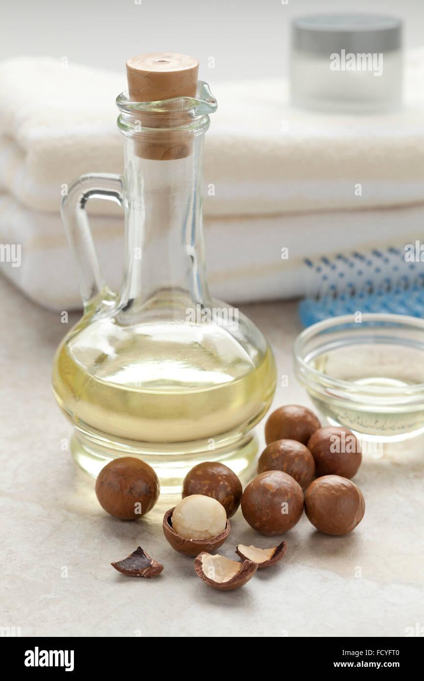 Flasche mit kosmetischen Macadamia-Öl und Nüssen Stockbild