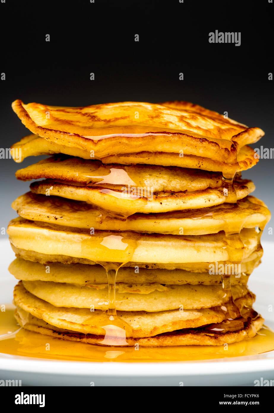 Stapel von Pfannkuchen auf weißen Teller beträufelt mit Sirup Stockbild