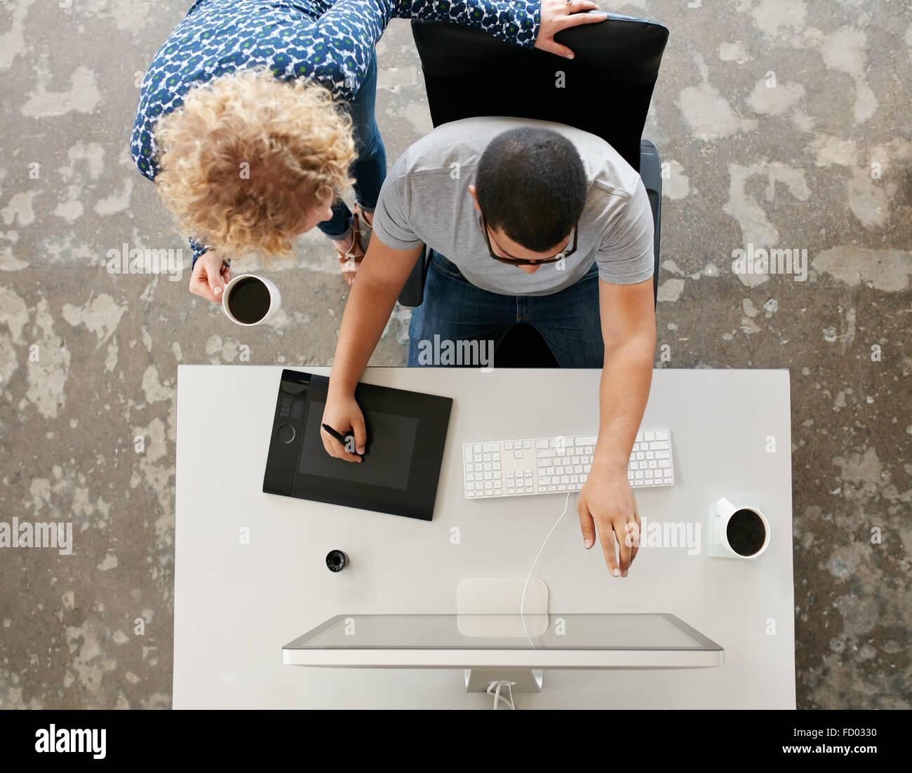 Draufsicht der junge Grafik-Designer arbeiten im Büro. Verwendung von digitalisierten Grafiktablett, digitalisierte Stockbild