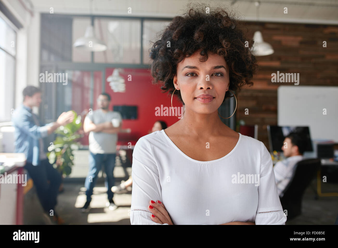 Porträt der Frau im geschäftigen Kreativbüro Blick in die Kamera. Attraktive weibliche Kreativ-Profis Stockbild