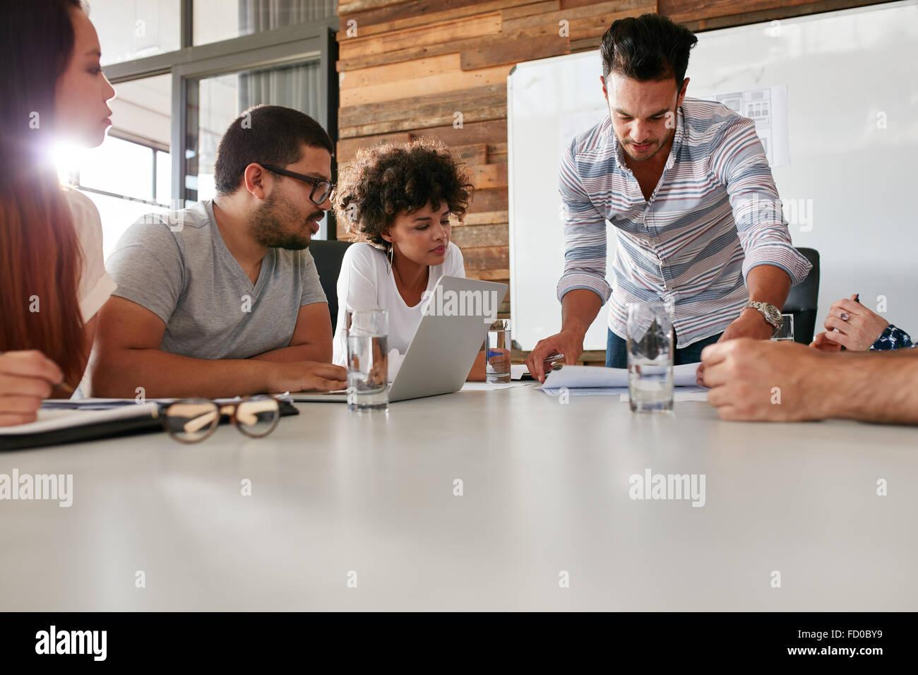 Junger Mann präsentieren ist Ideen mit Kollegen während Meetings im Konferenzraum. Führer zeigen Stockbild