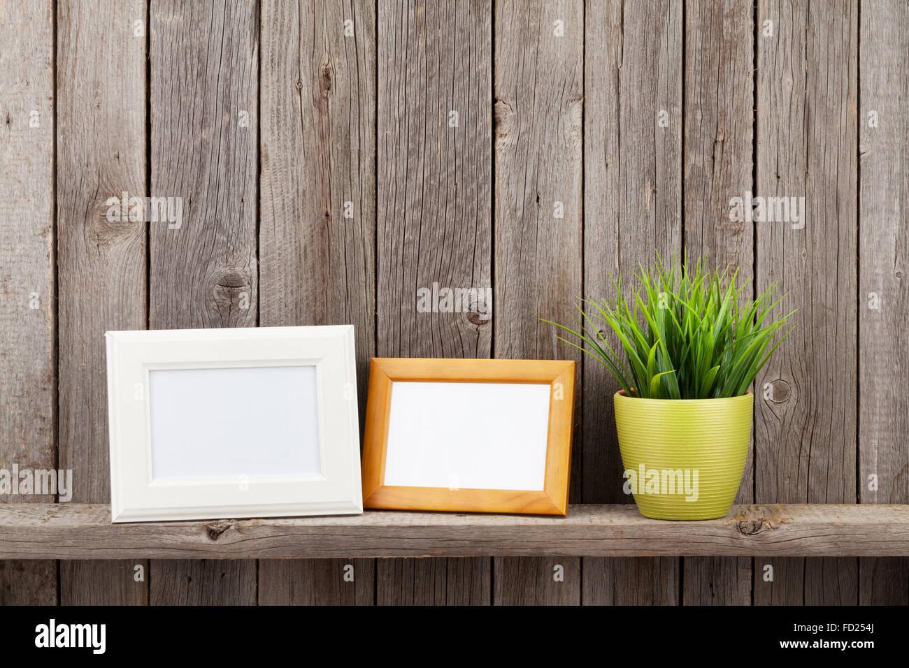Leere Bilderrahmen und Pflanzen auf Regal vor Holzwand Stockfoto ...
