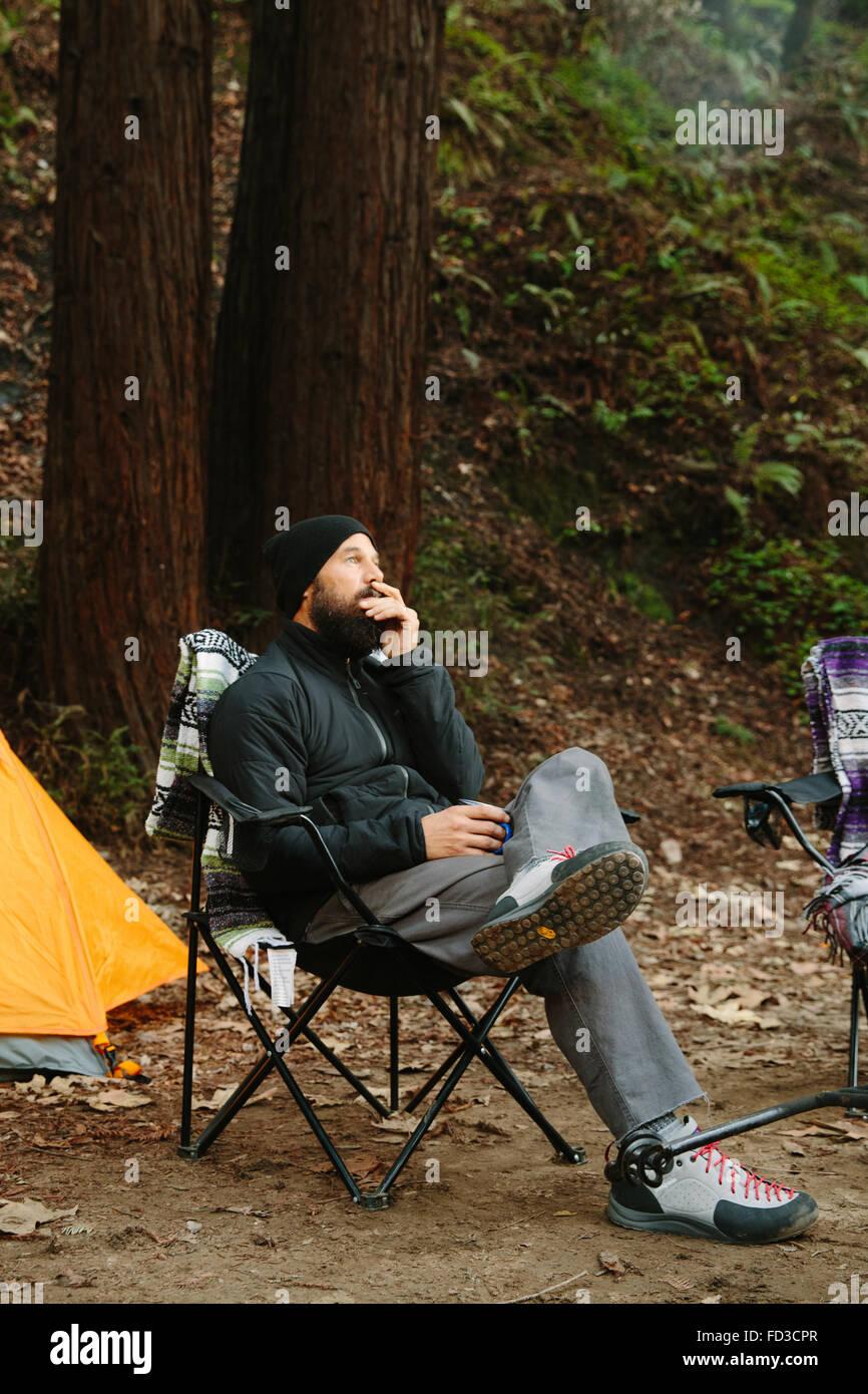Ein junger Mann sitzt auf dem Campingplatz in Big Sur, Kalifornien. Stockbild