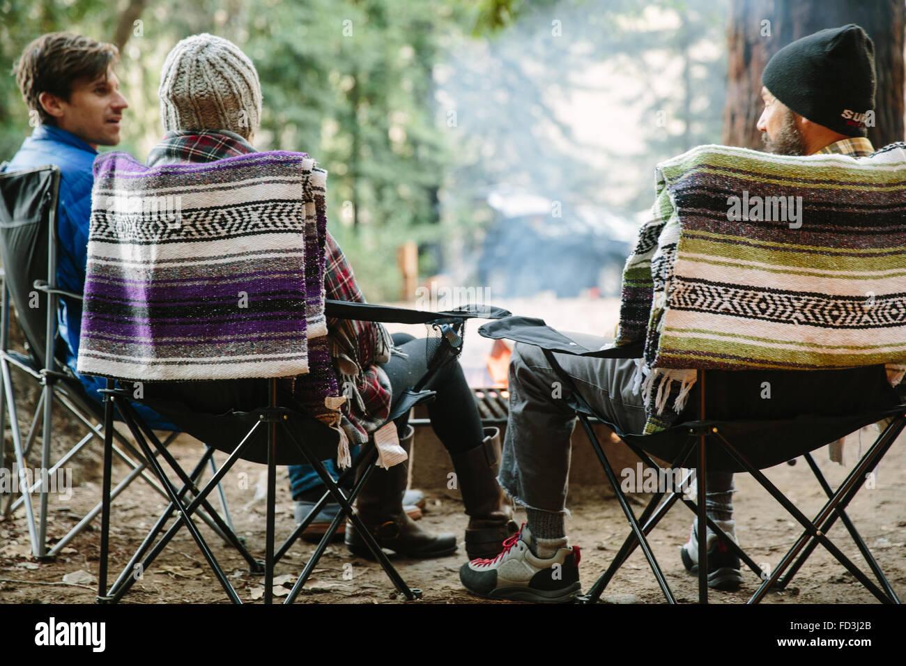 Drei Freunde sitzen um ein Lagerfeuer in Big Sur, Kalifornien. Stockbild