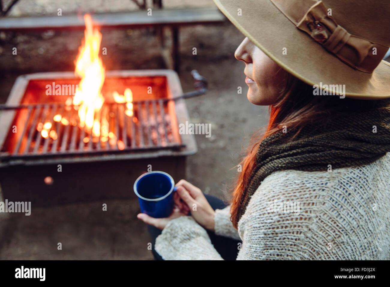 Frau genießt einen Lagerfeuer Moment mit Kaffeetasse Stockbild