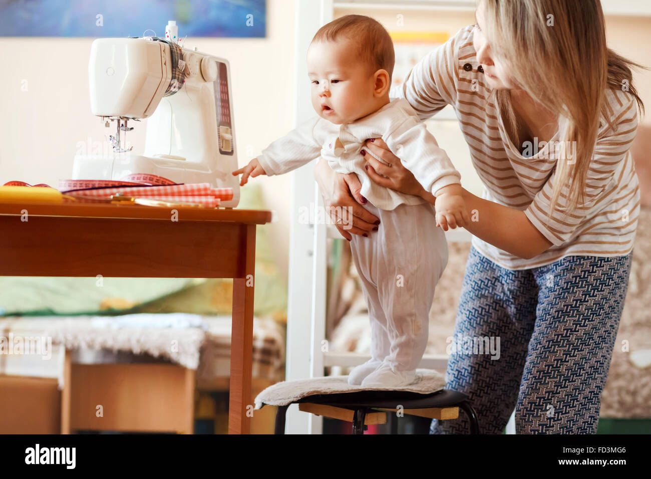 Mutter und Kind, zu Hause, die erste Gehversuche, natürliches Licht. Baby-/Kinderbetreuung kombiniert mit Arbeit Stockbild