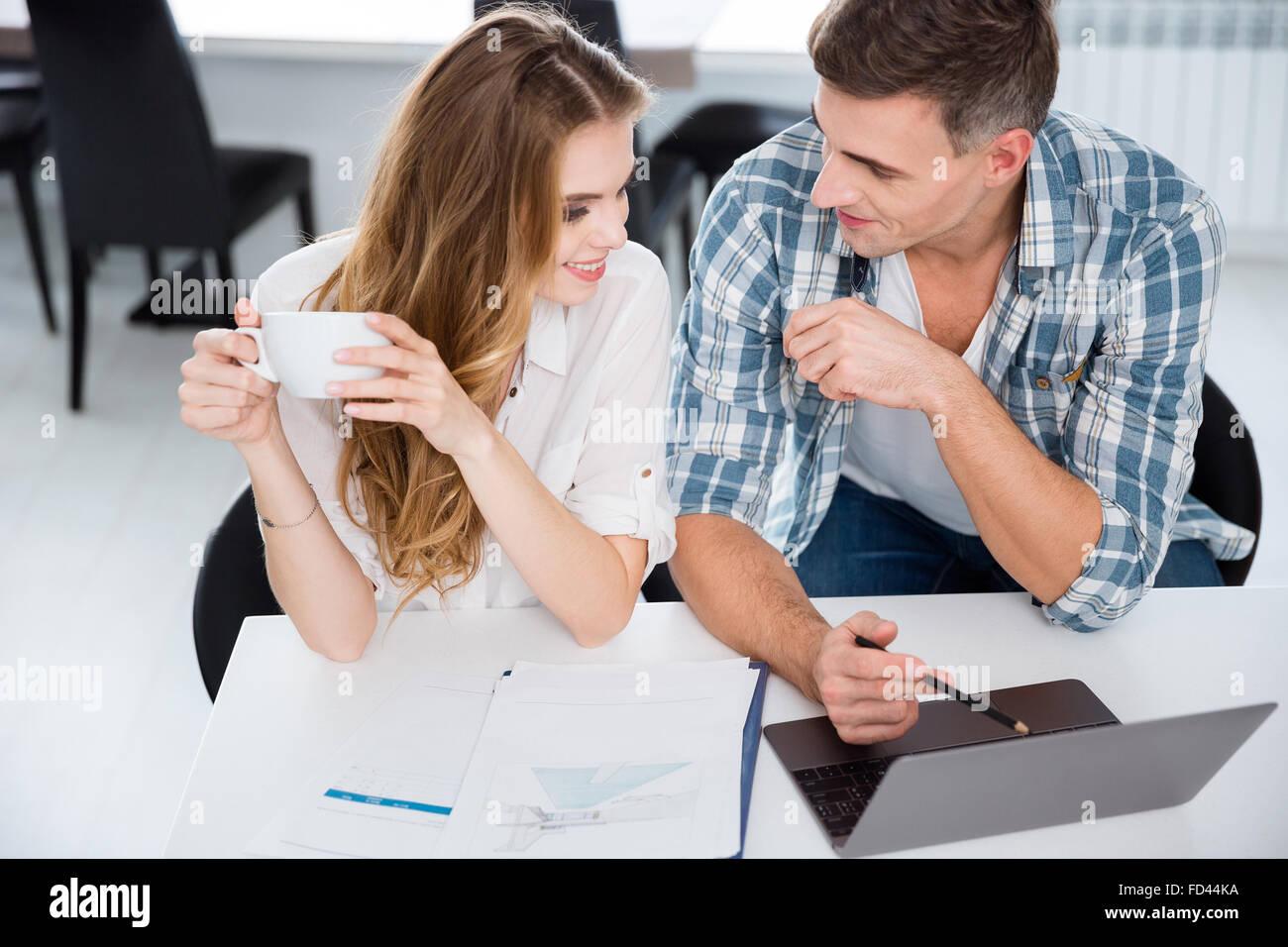 Glückliche Kollegen im Büro sitzen und gemeinsam mit laptop Stockbild