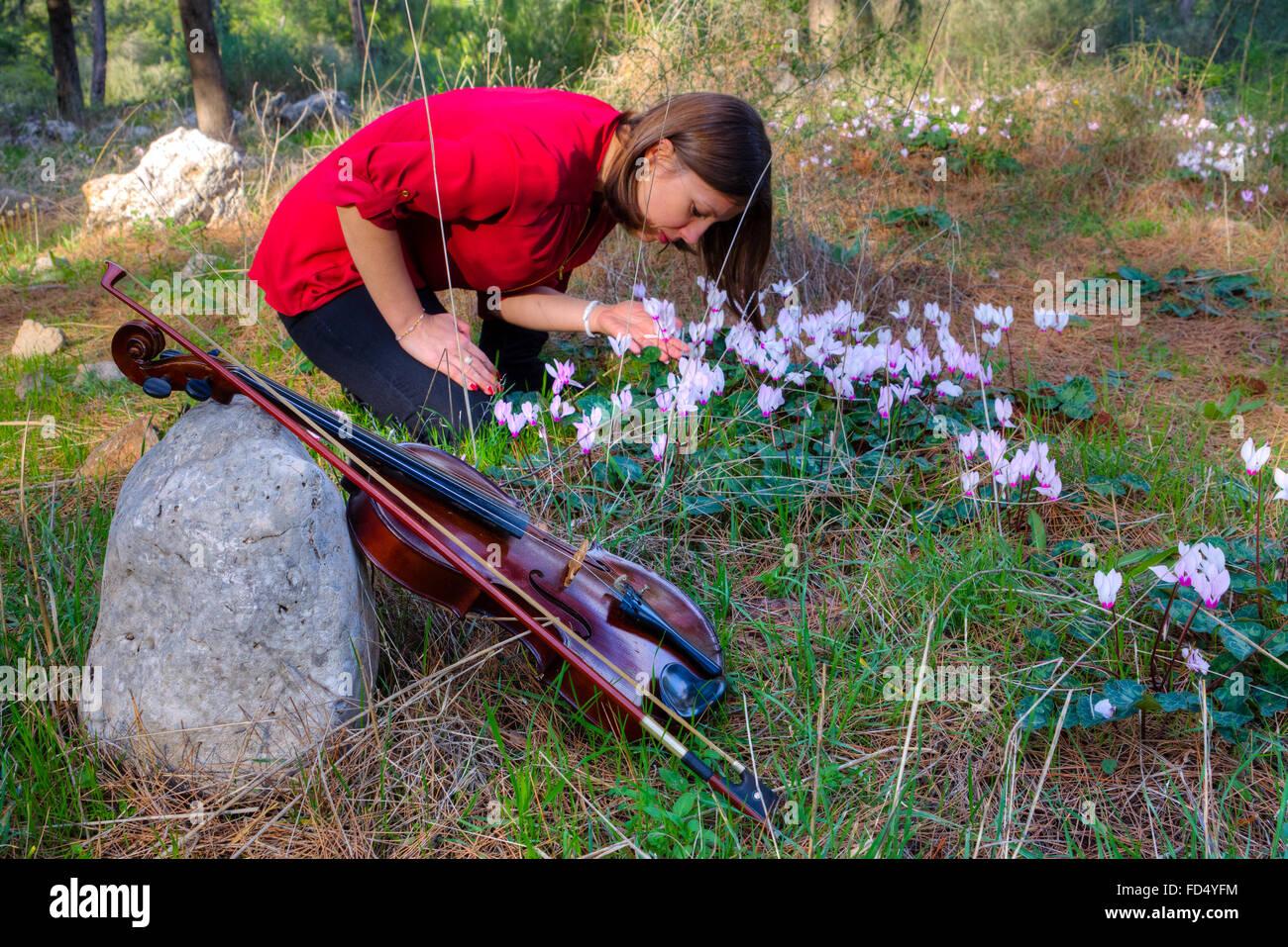 Mädchen hat Violine und sammelt Blumen. Kleine Schärfentiefe Stockbild
