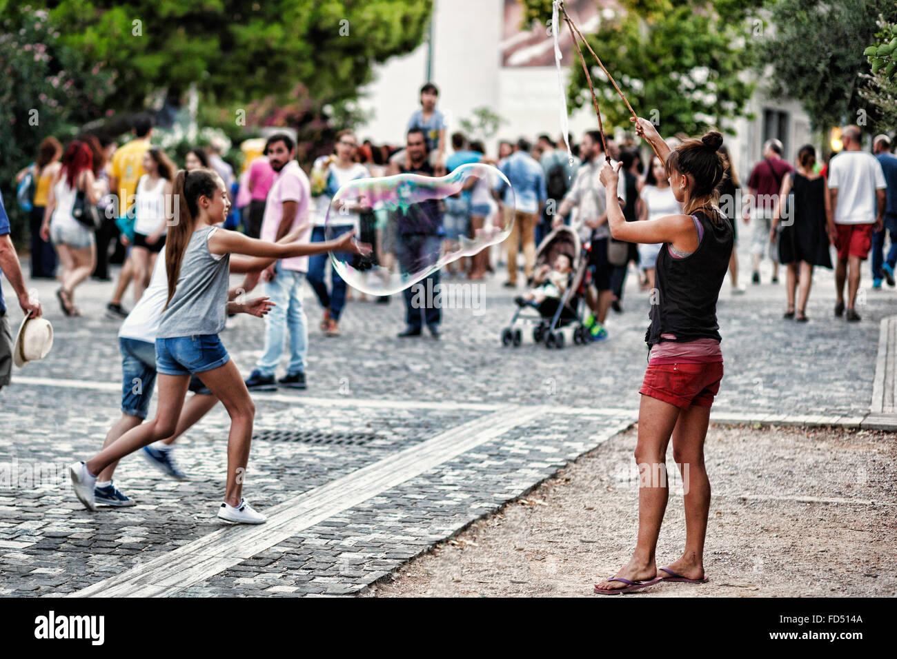 Kleine Kinder spielen mit riesige Seifenblasen in den Straßen von Athen, Griechenland Stockbild
